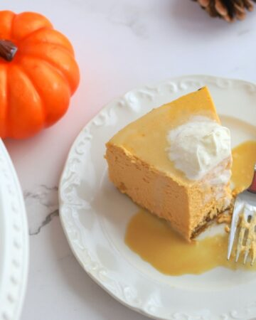 slice of pumpkin cheesecake with a fork topped with whipping cream
