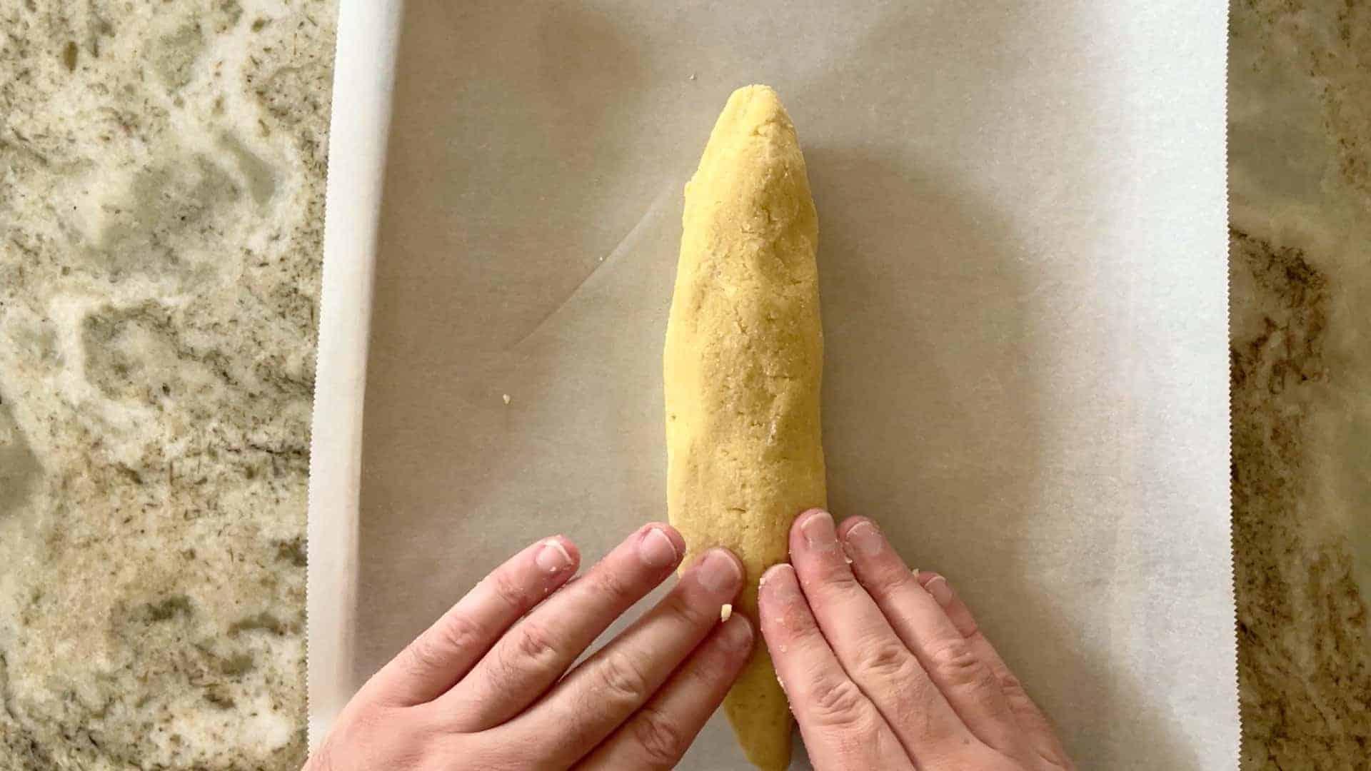 shaping the baguette dough on the baking sheet