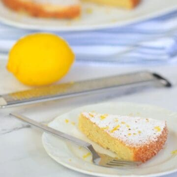 slice of lemon cake on a plate with lemon and lemon zester