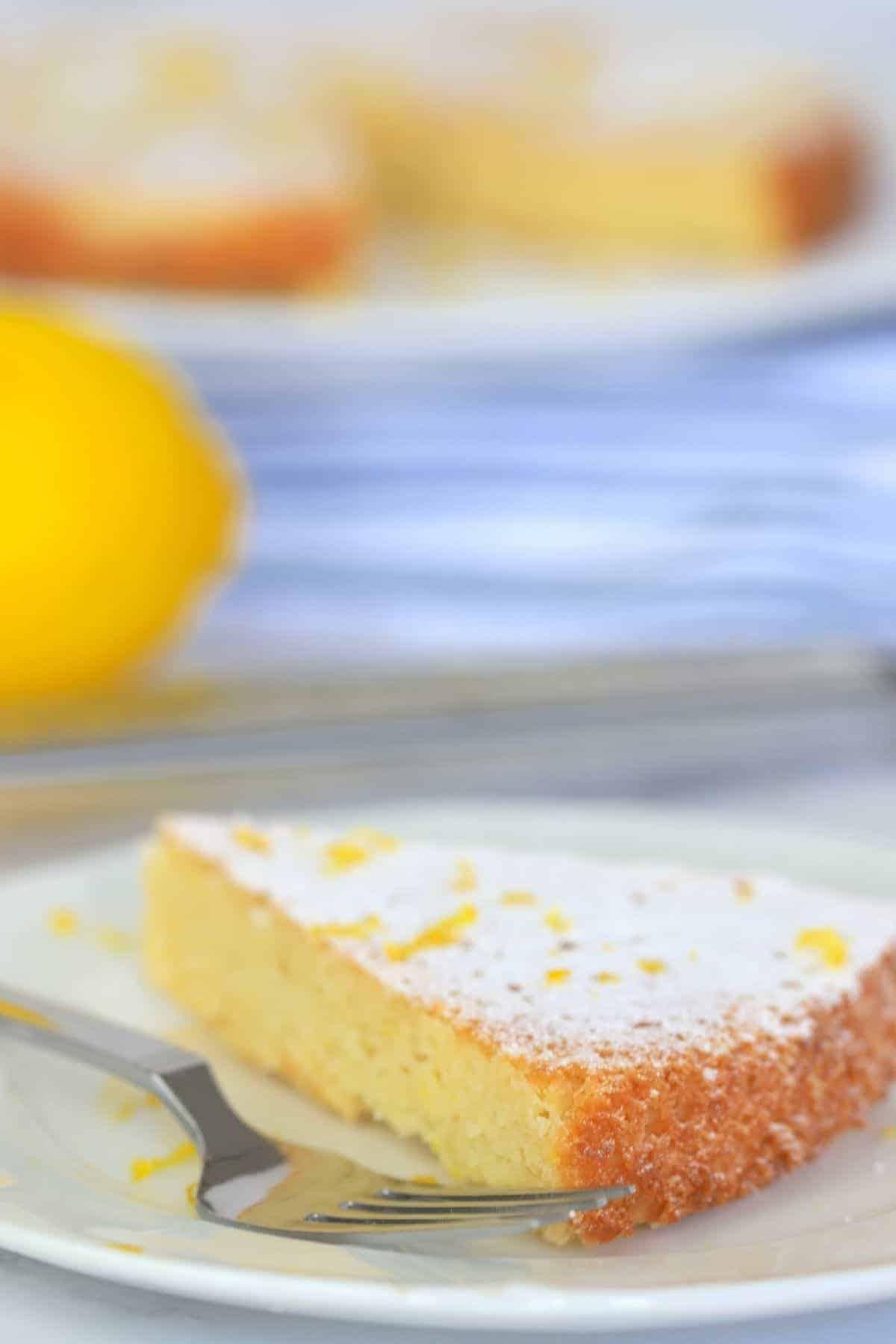 Lemon cake on a plate next to a lemon and lemon zester