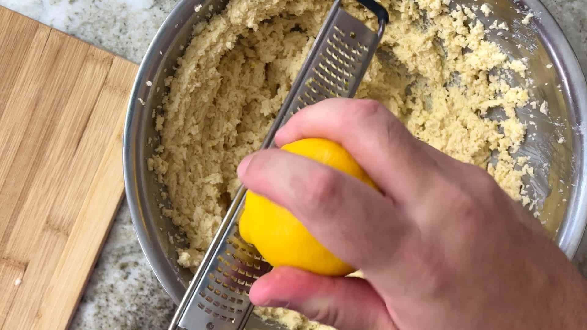 zesting a lemon into the cake batter
