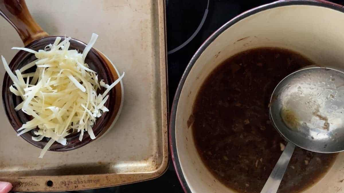 a bowl of french onion soup topped with cheese next to pot of soup with a ladle in it